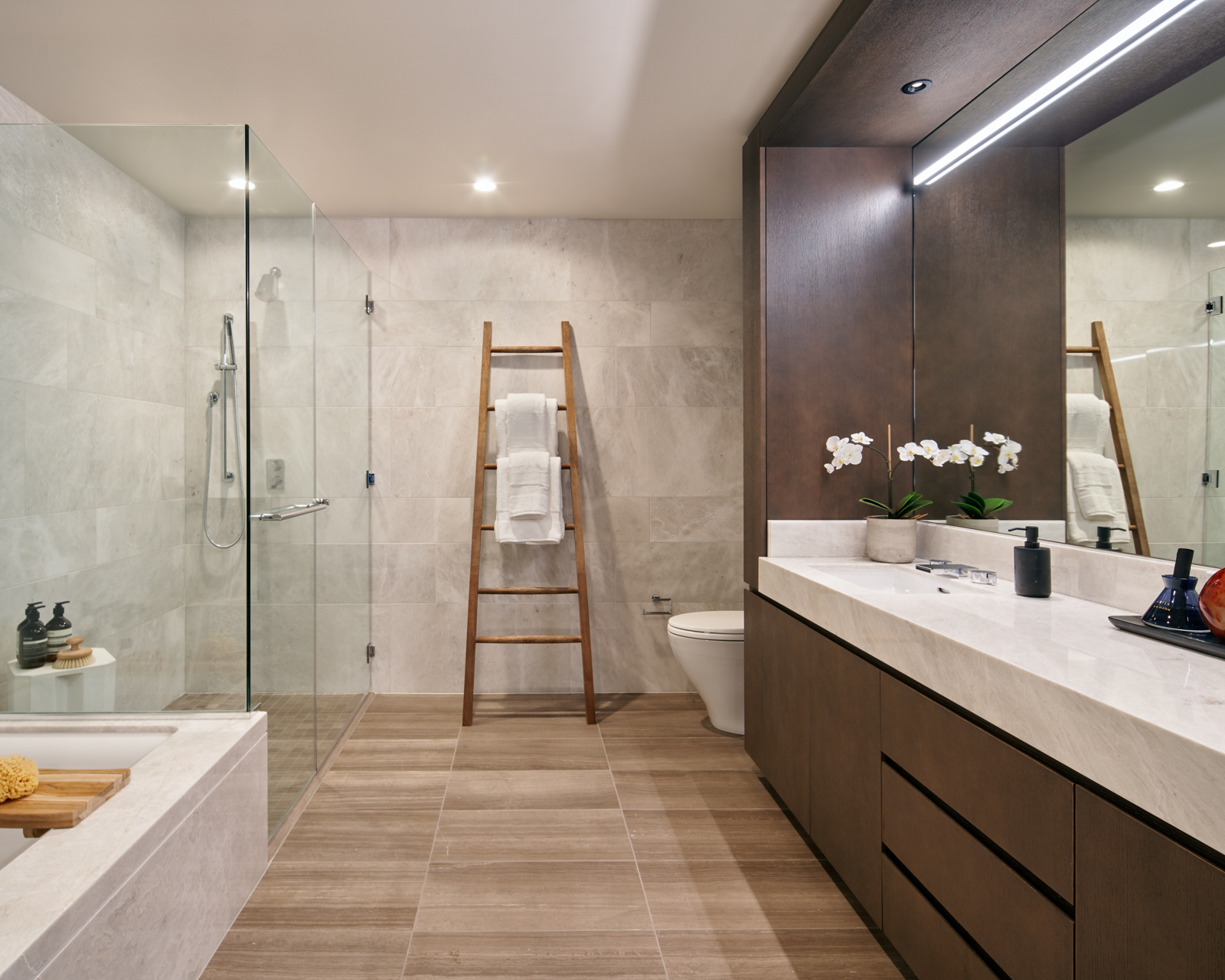 Sumptuous master baths appointed with elegant stone and warm wood tones